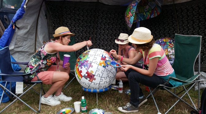 Ladies painting a piece of a globe