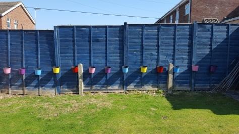 Colourful pots along a fence